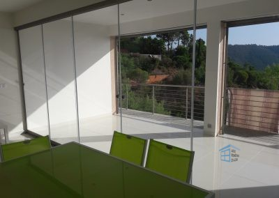 Fermeture d'un grand balcon avec un rideau de verre