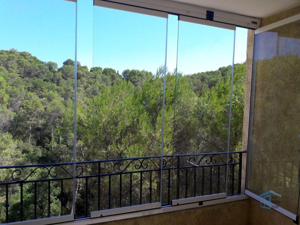 Rideau de verre entrouvert sur balcon
